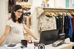 Pregenant woman orking in clothes store Royalty Free Stock Images