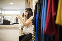 Pregenant woman orking in clothes store Stock Image
