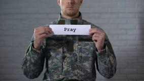 Preghi la parola scritta sulle mani del segno dentro del soldato maschio, meccanico che chiede la pace archivi video