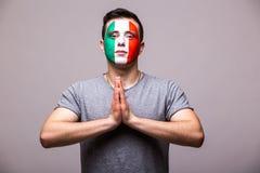 Preghi per l'Italia Il tifoso italiano prega per la squadra nazionale dell'Italia del gioco su fondo grigio Fotografie Stock