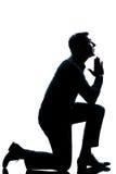 Preghiera di inginocchiamento dell'uomo della siluetta integrale immagine stock libera da diritti