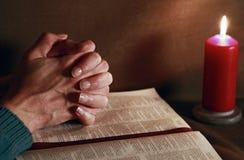 Preghiera e bibbia con la candela bruciante immagini stock