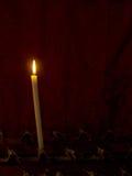 Preghiera La singola candela della chiesa brucia davanti alla tenda rossa Appunto Fotografie Stock Libere da Diritti