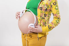 Pregnan woman in casual outfit cherish her belly with headphones Royalty Free Stock Photos