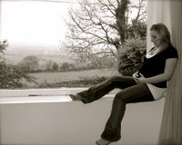 Pregnancy. A pretty pregnant girl, sitting in the window royalty free stock image