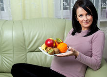 Pregnancy. Pregnant woman with plate of healthy fruit stock photo