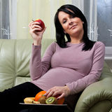 Pregnancy. Pregnant woman with plate of healthy fruit royalty free stock photo