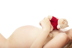 Pregnancy. Close-up photo of the pregnant woman laying on a white background and holding Teddy Bear toy Stock Photos