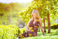 Pregnancy. Beautiful pregnant female in park stock photos