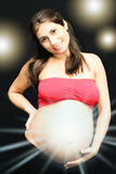 Pregnancy. Pregnant woman with the hand in the womb with light rays Stock Photo