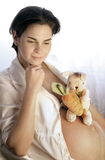 Pregnancy. A pregnant women is waiting for the baby. She already has a toy rabbit who is also waiting for the young newcomer Royalty Free Stock Images