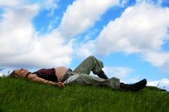 Pregnancy. A young pregnant woman lying on a meadow in front of a easily cloudy sky Royalty Free Stock Image