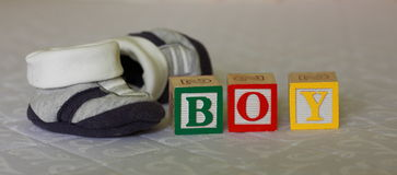 Pregnancy - baby blocks and baby shoes. ColorfuL blocks of wood sing - BOY - while expecting a baby with the baby bed and shoes in the background Royalty Free Stock Image