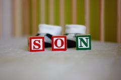 Pregnancy - baby boy blocks and baby shoes - son. Coloured blocks of wood sing - SON - while expecting a baby with the baby bed and shoes in the background Stock Images