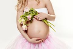 Pregnancy. Exposed belly and hands of a pregnant woman. Spring flowers. Tulips. royalty free stock image