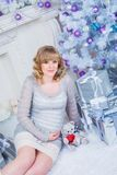 Pregnancy and Christmas, people and expectation concept - happy pregnant woman touching her belly. Stock Image