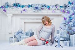 Pregnancy and Christmas, people and expectation concept - happy pregnant woman touching her belly. Stock Images