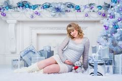 Pregnancy and Christmas, people and expectation concept - happy pregnant woman touching her belly. Royalty Free Stock Photography