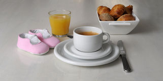 Pregnancy concept baby shoes on breakfast table Stock Photos