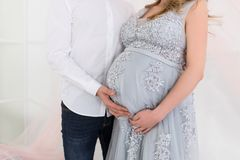 Pregnancy concept - couple hugging the pregnant belly. Hands of family members holding a belly of pregnant woman. Maternity Stock Images