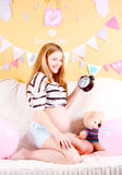 Pregnancy concept. happy pregnant woman with an alarm clock at h Royalty Free Stock Photo