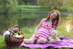 Pregnancy Concept. Pregnant woman. Pregnant woman relaxing and listening to music near the lake. She is sitting on the grass and closed her eyes Stock Images