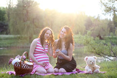 Pregnancy Concept. Relax in nature. Two women sitting near a river in the rays of sunset. Pregnant women and her sister listen to music. Full relax. Weekend Royalty Free Stock Photography