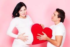Pregnant couple with heart Stock Photos