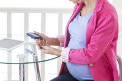 Pregnancy diabetes- Pregnant woman taking a blood sample glucose level Stock Photo