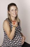 Pregnancy diet. Smiling pregnant woman eating a red apple stock photo
