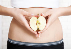 Pregnancy or diet concept, female hands holding apple. Stock Images
