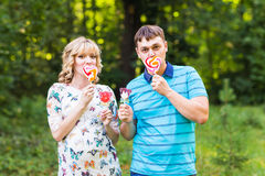 Pregnancy, family, happiness and fun concept - Man and pregnant woman have fun with candy in the park Stock Photography