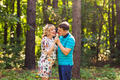 Pregnancy, family, happiness and fun concept - Man and pregnant woman have fun with candy in the park Royalty Free Stock Photo