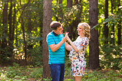 Pregnancy, family, happiness and fun concept - Man and pregnant woman have fun with candy in the park Stock Images