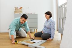 Family couple assembling baby bed at home royalty free stock photos