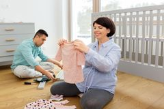 Family couple preparing for baby birth at home. Pregnancy, family and nursery concept - happy middle-aged pregnant women reviewing baby clothes and her husband royalty free stock photos