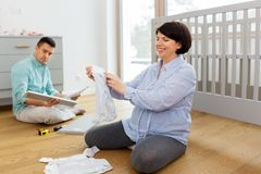 Family couple preparing for baby birth at home. Pregnancy, family and nursery concept - happy middle-aged pregnant women reviewing baby clothes and her husband royalty free stock image