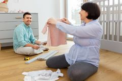Family couple preparing for baby birth at home. Pregnancy, family and nursery concept - happy middle-aged pregnant women showing baby clothes to her husband stock photography