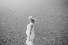 Pregnancy and fertility. Motherhood and maternity concept. Pregnant woman in white dress walking on sea beach on sunny day on blue water. Mother with big belly royalty free stock photo