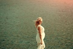 Pregnancy and fertility. Motherhood and maternity concept. Pregnant woman in white dress walking on sea beach on sunny day on blue water. Mother with big belly royalty free stock image