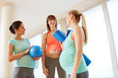 Pregnant women with sports equipment in gym royalty free stock images
