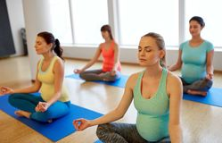 Happy pregnant women meditating at gym yoga royalty free stock photos
