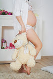 Pregnancy and  fleecy bear toy Stock Photography
