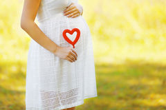 Pregnancy, maternity and new family concept - pregnant woman. And heart symbol outdoors in sunny summer day royalty free stock photography