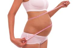 Pregnancy. Measure the belly with a centimeter tape. royalty free stock photos
