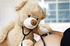 Pregnancy, medicine and healthcare concept - close up of Teddy bear playing doctor stethoscope and listens to her mother`s stock photo