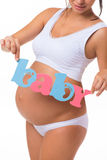 Pregnancy. Motherhood. Blue and pink text «Baby» on pregnant belly. Royalty Free Stock Image