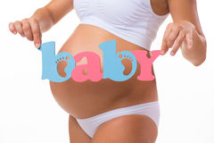 Pregnancy. Motherhood. Blue and pink word «Baby» near the pregnant tummy. Royalty Free Stock Photos