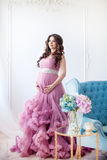 Pregnancy, motherhood and expectation concept - a pregnant woman dressed in a beautiful pink dress Stock Image