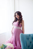 Pregnancy, motherhood and expectation concept - a pregnant woman dressed in the beautiful pink evening dress smiles Stock Photo